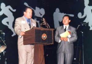 12 Tommy with Bob Park speaking at Korean - American Amateur Sports Association event, 1997